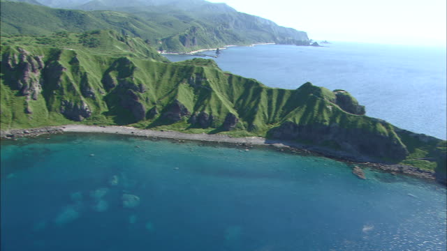 Cape Kamui rising in the westernmost part of Shakotan Peninsula Wide and Long Aerial Shot Dolly Shot from foot of the cape to its top further to The...