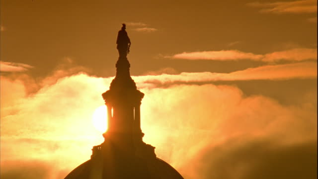 WS Capitol Building dome top Statue of Freedom w/ sun BG moving clouds in burnt orange yellow sky