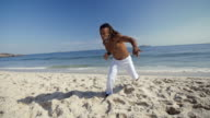 Capoeira artist on Ipanema Beach runs and jumps into flying punch towards camera