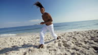 Capoeira master throws punch at camera and spins in the sand on Ipanema Beach