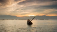 capsize fishing boat on the sea at sunset