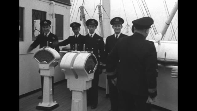 Captain James Bisset of the RMS Queen Elizabeth on deck / Bisset descends stairs and salutes 5 crew officers / Bisset smiling and talking with...
