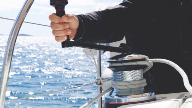 MS-Kapitän anziehen das Seil um eine Seilwinde auf einem Segelboot