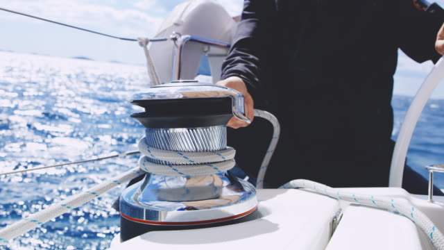 MS Captain tightening the rope around a winch on a sailing sailboat