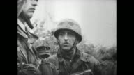 [Captured German footage VO music and French language throughout] Soldiers in trench / CU soldier with foliage camouflage on his helmet / explosion /...