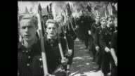 [Captured German footage VO music and French language throughout] Division of Hitler Youth run to line up in formation / VS individual young men...