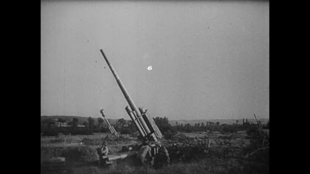 [Captured German footage VO music and French language throughout] Squadrons of fighter planes fly high in sky / antiaircraft guns fire in unison /...