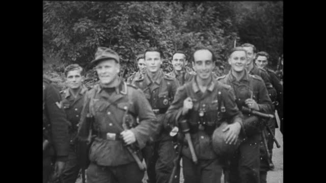 [Captured German footage VO music and French language throughout] VS German and possibly Vichy French soldiers march on road approaching camera horse...