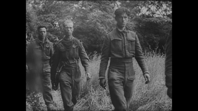 [Captured German footage VO music and narration in French] VS captured Allied prisoners of war walk / CU insignia on sleeve 'Durham Light Infantry' /...