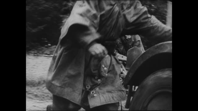 [Captured German footage VO music and narration in unknown language] VS German military vehicles covered with foliage move on road / soldier trots on...