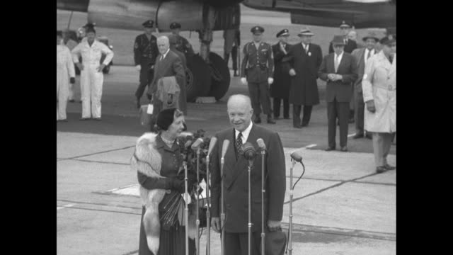 Car carrying Presidentelect Dwight Eisenhower and his wife Mamie parked next to plane at airfield / Eisenhower and Mamie walking towards plane /...
