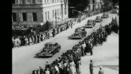 Car carrying Soviet Foreign Minister Molotov driving away from airport past camera / motorcade driving down street crowds on either side watching /...