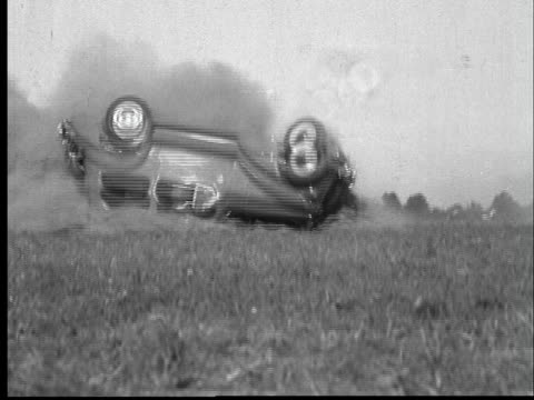B/W MONTAGE 1936 Car crashing and rolling on field, people coming to help