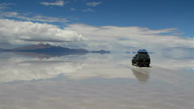 Car crossing the vast salt desert covered with a mirror like film of water after rain. Bolivia, Salar de Uyuni
