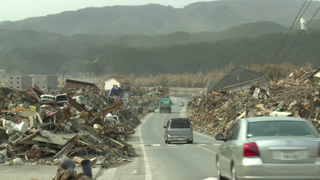 Car drive along road bulldozed clear of deris through remains of Rikuzentakata city, Iwate Prefecture, Japan on 2nd April 2011; 3 weeks after the tsunami following the Tohuku earthquake of March 2011.