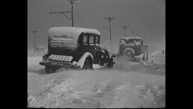 Car drives on road past snowdrift in foreground / LS down snowcovered road / snowcovered cars parked in snowdrifts / rear shot traffic moves slowly...