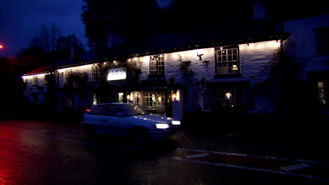 A car drives past a pub at night Available in HD.
