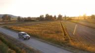 Luchtfoto auto rijden langs een weg van het platteland in de zonsondergang