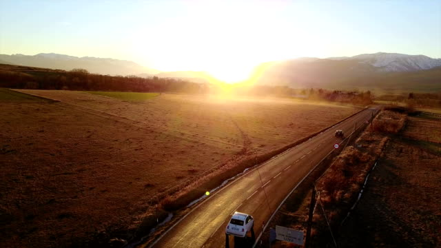 Car driving along a countryside road in sunset