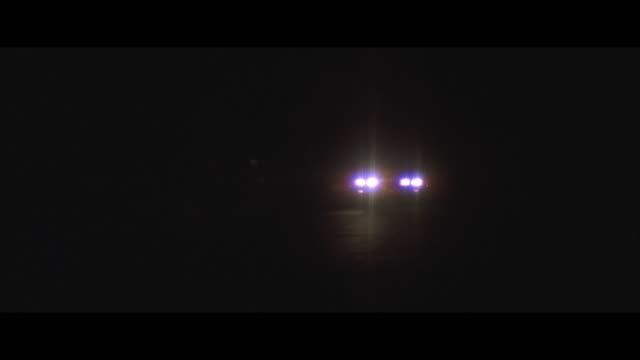 WS, PAN, Car driving on desert road at night, thin cloud covering full moon, USA