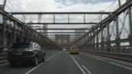 Car POV driving over Brooklyn Bridge heading towards Manhattan