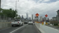 Car POV driving over Brooklyn Bridge heading towards Manhattan with NYC skyline on the horizon