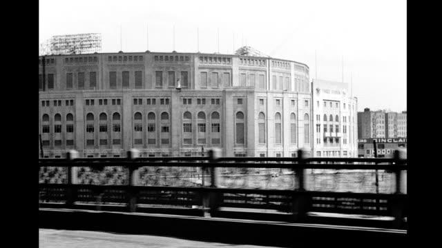 Car POV driving past Yankee Stadium onto the Macombs Dam Bridge over the Harlem river into Manhattan Car POV over Harlem River near Yankee Stadium on...