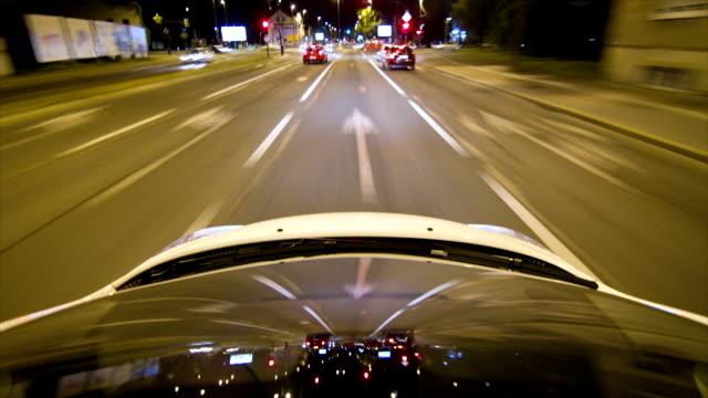 Car driving through the city at night