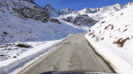 T/L of car driving up snowy and winding mountain road