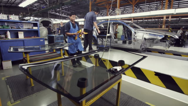 WS Car factory worker applying silicon seal to windshield on production line / Samut Prakan, Bang Muang Mai, Thailand