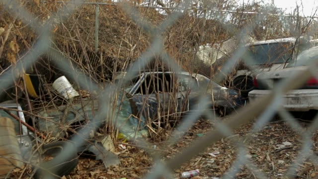 Car junk yard with fence in foreground slow motion
