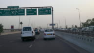 T/L POV of car, leaving Delhi towards Gurgaon on National Highway 8 or NH8, crossing the airport in-between