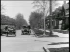 B/W 1919 car making sharp left turn on residential street + cutting off other car / newsreel
