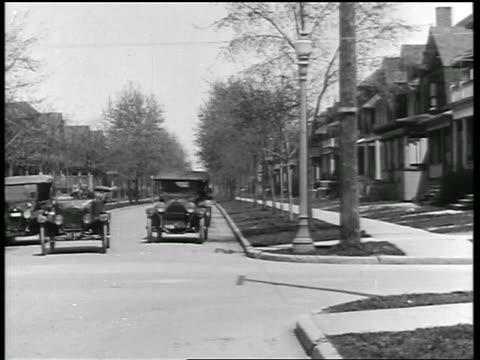 B/W 1919 car making sharp left turn on residential street + cutting off other car / newsreel
