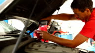 Car mechanic pouring fresh engine oil.