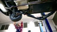Meccanico auto, lavorando sotto un veicolo.