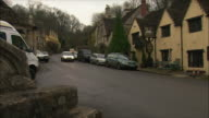 WS PAN Car on road crossing old village with cotswolds stone buildings / United Kingdom