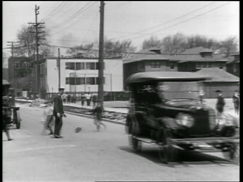 B/W 1919 car passing children crossing street as traffic cop stands by / newsreel