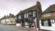 MS Car passing in front of exterior tudor-style pub / St Albans, Hertfordshire, United Kingdom