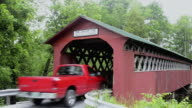 MS Car passing through red wooden covered bridges of Vermont by river One Dollar Fine Chiselville Bridge / Arlington, Vermont, United States