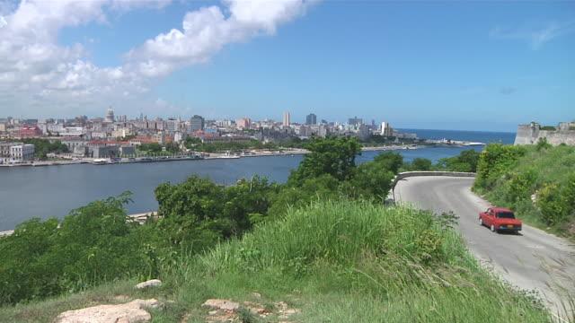 WS Car passing with Havana skyline in distance / Havana, Havana, Cuba