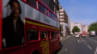 Car point of view double decker buses passing on left on London street / London, England