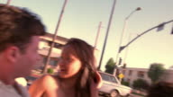 Car point of view group of young people laughing and riding in convertible on residential street / Los Angeles