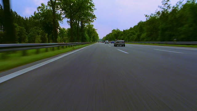 Car point of view in traffic on autobahn lined by trees / tilt up tilt down sky / Germany