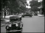 B/W 1928 REAR car point of view Lincoln car driving on suburban street / Detroit, Michigan / newsreel