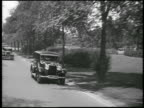B/W 1928 REAR car point of view Lincoln car passing on street / Detroit, Michigan / newsreel