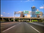 Car point of view on highway under overpasses towards downtown Houston, Texas