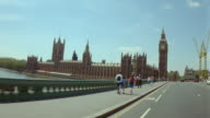 Car point of view over Thames on Westminster Bridge toward Big Ben + Parliament / London, England