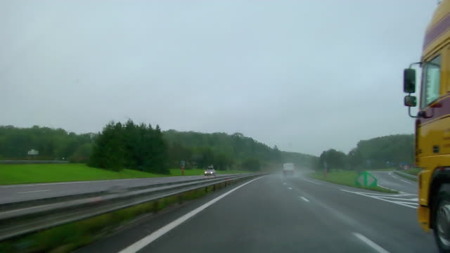 Car point of view passing trucks traveling on A4 autoroute between Strasbourg and Metz on rainy day / France