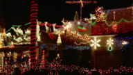 Car point of view past houses decorated with Christmas lights / night / California